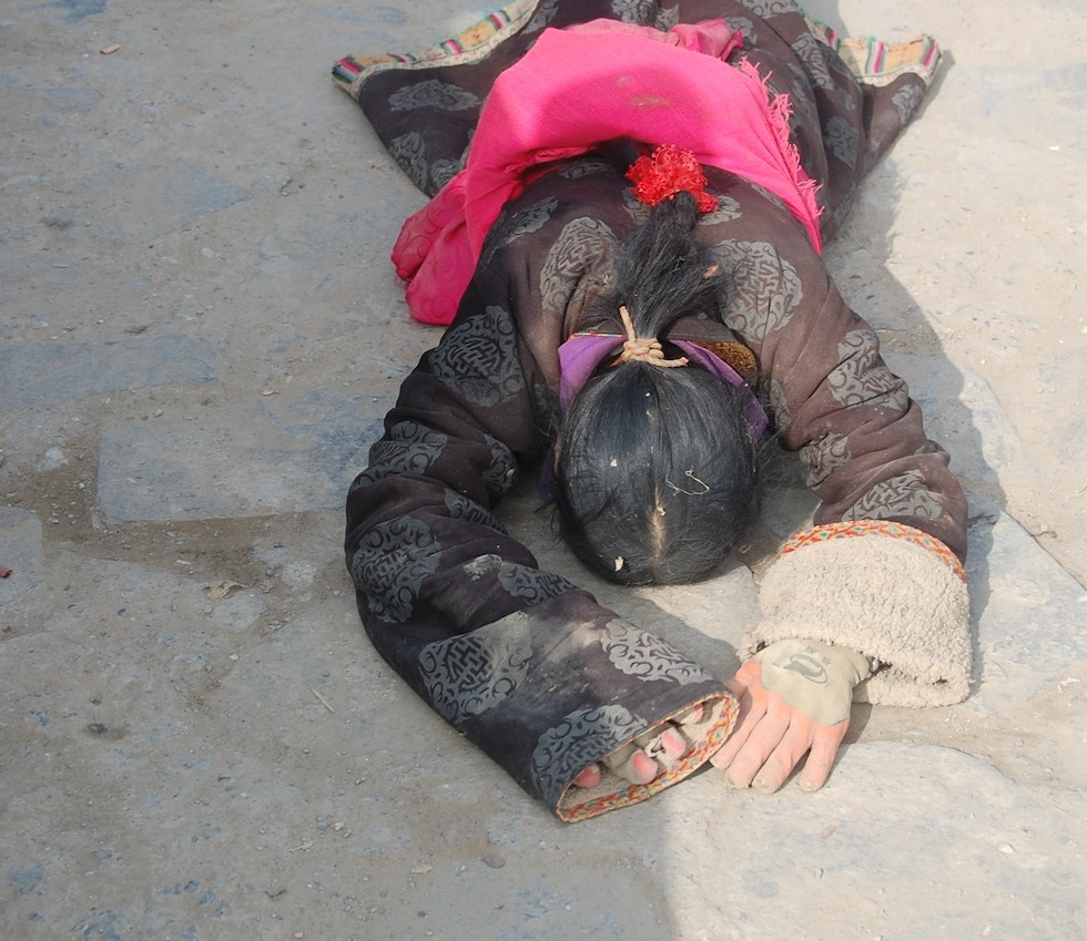 Tibetan woman is doing full body prostrations in the monastery.